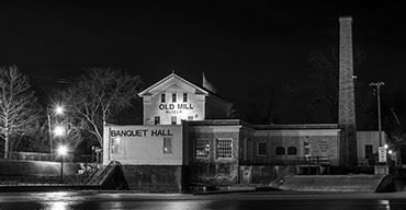 An old building and with a sign saying banquet hall in black and white